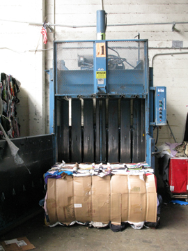 a baler with a bale of clothing to be sold for scrap