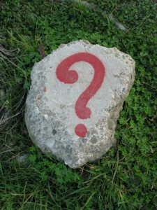 a red question mark painted on a piece of concrete