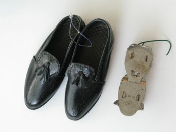tiny black loafers and an old-school metal roller skate