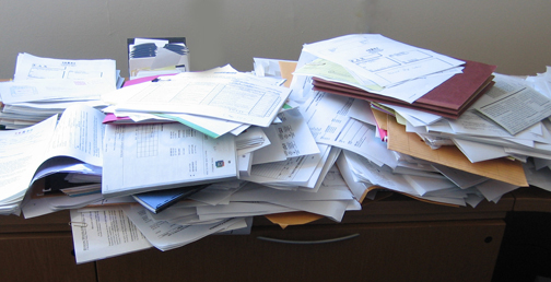 a messy desk covered with piles of paper