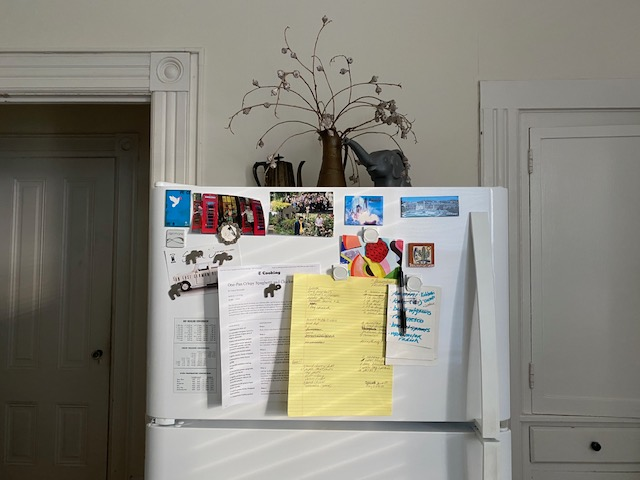 Freezer door with papers and photos magnetized to the facade.